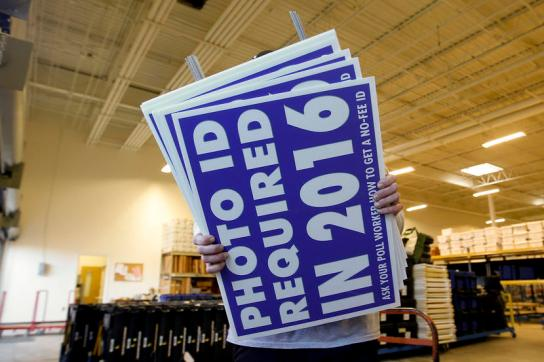 A worker carries a sign that will be displayed at a polling place that will inform voters of the new voter ID law that goes into effect in 2016 at the Mecklenburg County Board of Elections warehouse in Charlotte